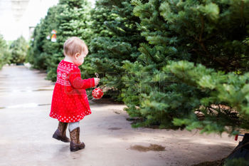 34394432-cute-baby-girl-in-red-scandinavian-dress-at-the-christmas-tree-farm